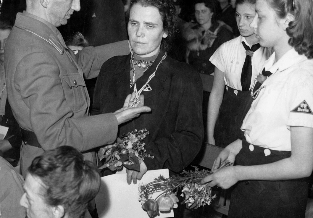 FIKK MEDALJE FOR ANTALL BARN: På dette bildet blir en mor tildelt et et gullkors under den tyske morsdagen i mai 1943. Det betyr at hun har født åtte barn eller flere. Til sammen 100 mødre fikk udelt kors denne dagen - ti gull og fem sølv.  Foto: NTB Scanpix
