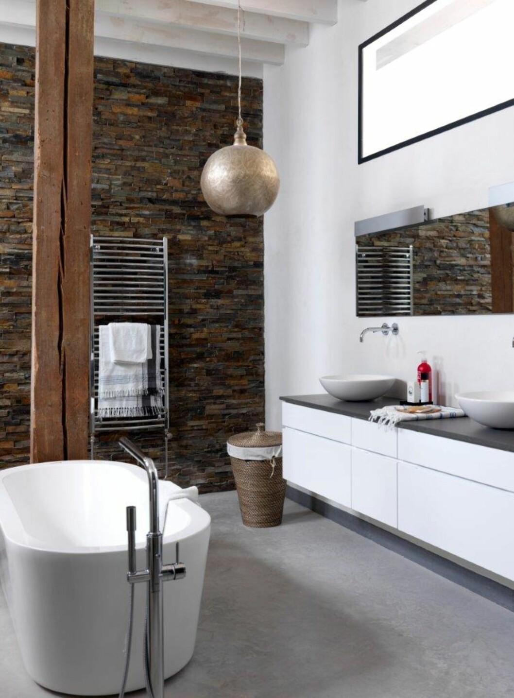SPENNENDE: Steinveggen, metallampen, og bruk av rått treverk og kurv gjør dettte baderommet alt annet enn kjedelig. Foto: IDECOR IMAGES
