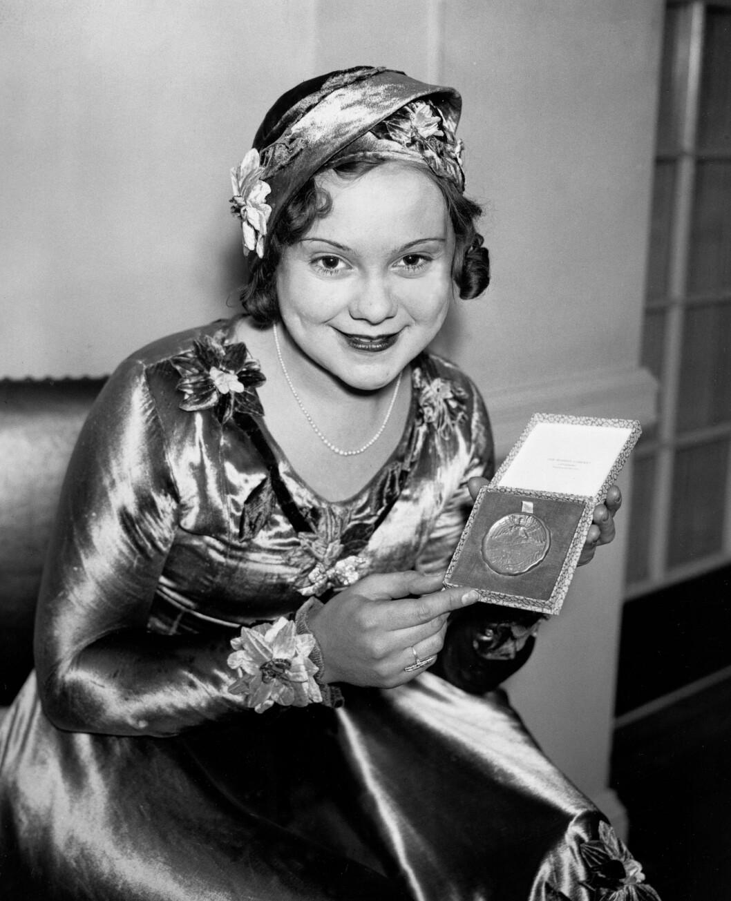 <strong>GULL OG MER GULL:</strong> Ennå ikke fylt 20 kan Sonja stolt vise fram sin andre olympiske gullmedalje i Lake Placid i 1932. Gull tok hun også i OL i St Moritz i 1928 og i Garmisch-Partenkirchen i 1936. Samme år ble hun profesjonell og dro til Hollywood, samtidig som hun turnerte med store, påkostede isshow i USA og Europa i perioden 1937-56. Hun ble den til da yngste nordmann som ble utnevnt til Ridder 1. klasse av St. Olavs Orden i 1937. Foto: NTB scanpix