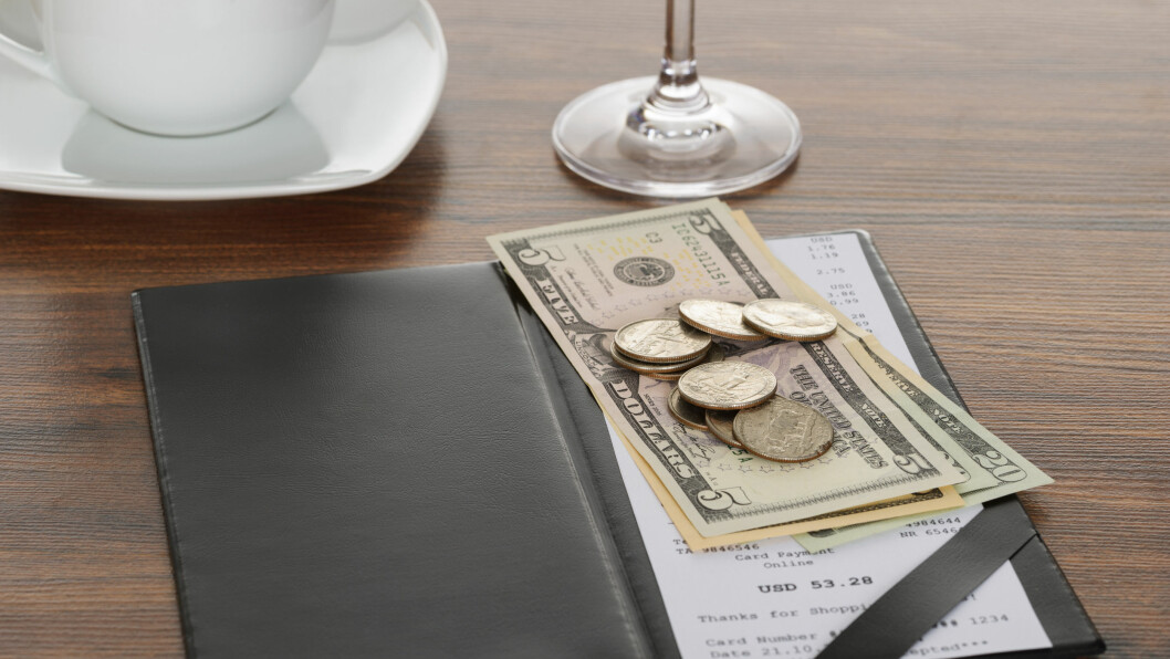 HVOR MYE SKAL MAN EGENTLIG TIPSE: Mange synes det er vanskelig å finne ut hvor mye man skal tipse, både hjemme og på ferie. Ifølge flyselskapet KLM varierer det hvor mye man skal gi i tips.  Foto: Shutterstock / Andrey_Popov