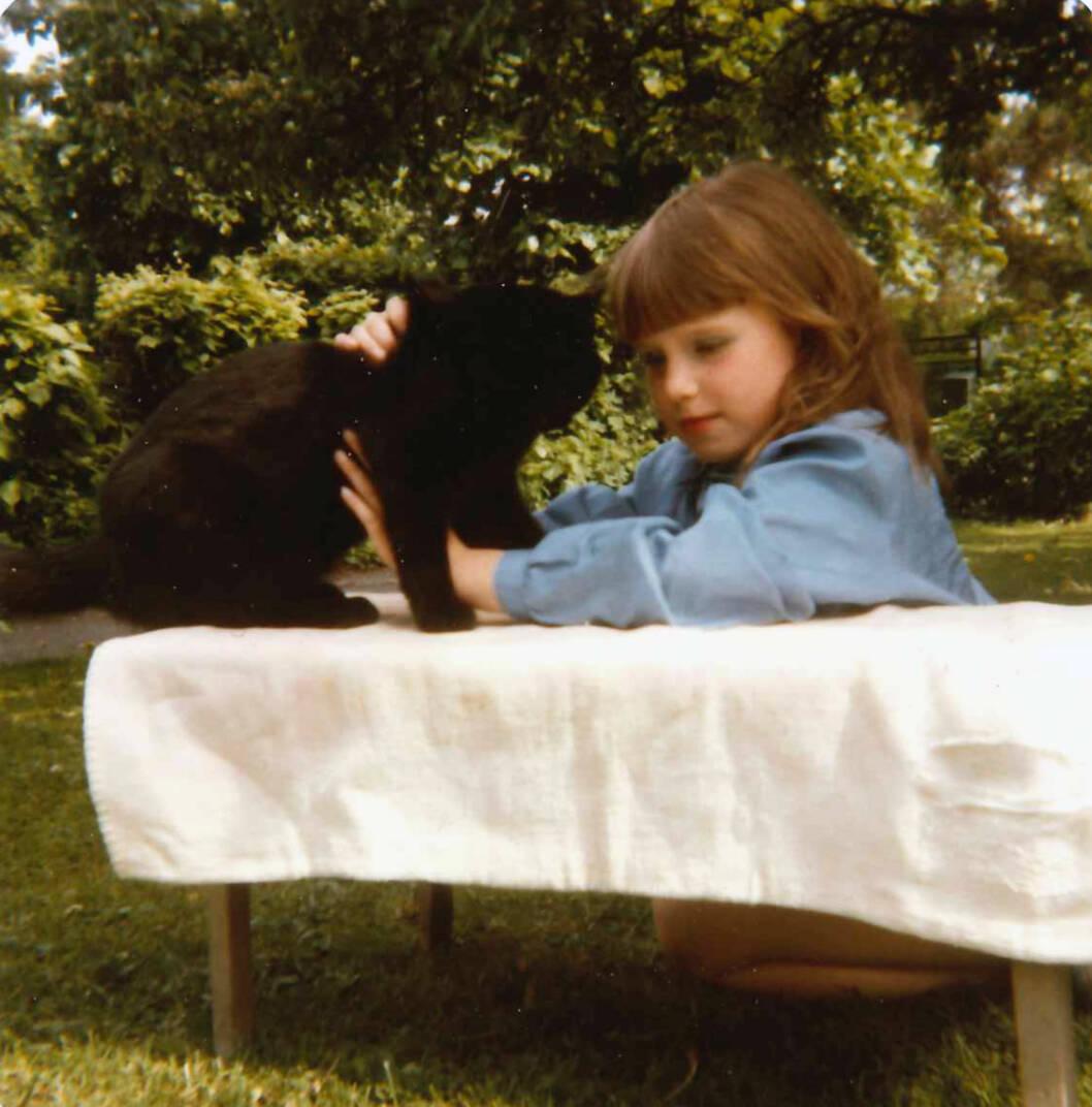 FINT MINNE: Ylva (8) prøver å posere som Mona Lisa, så kommer katten inn og forstyrrer – og det blir et fint og artig minne.. Foto: Privat