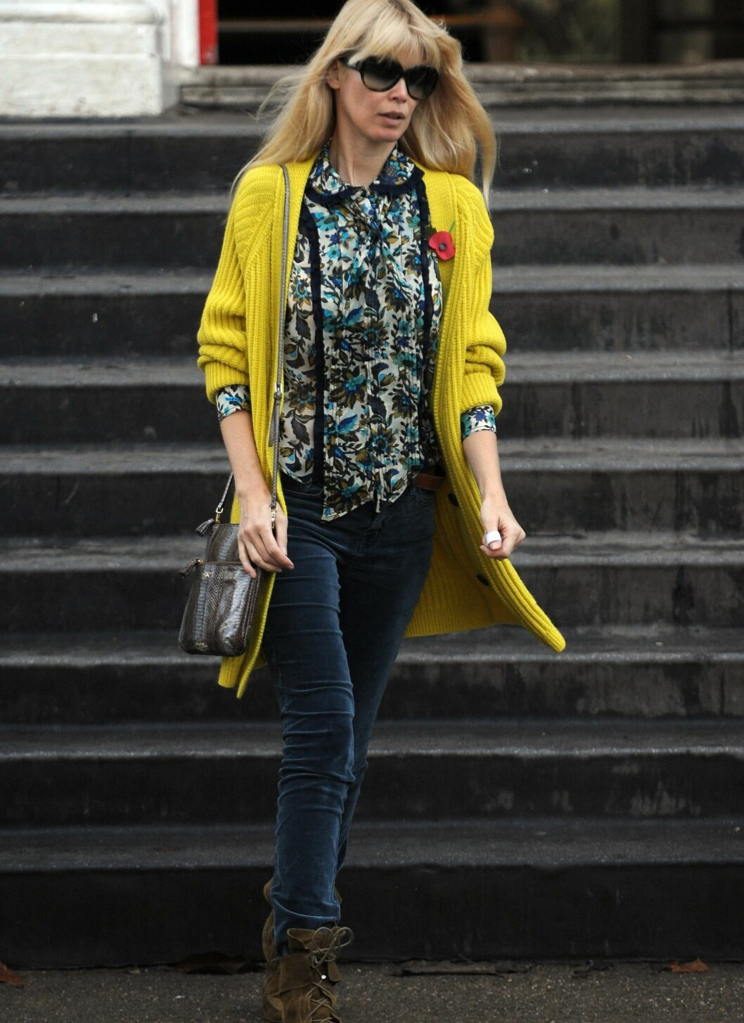 Model Claudia har en lett 70-tallsloook, der hun vandrer ut fra London-hjemmet sitt iført blå fløyelsbukser, mønstret bluse og en knallgul cardigan med blomster på brystet.  Foto: All Over Press
