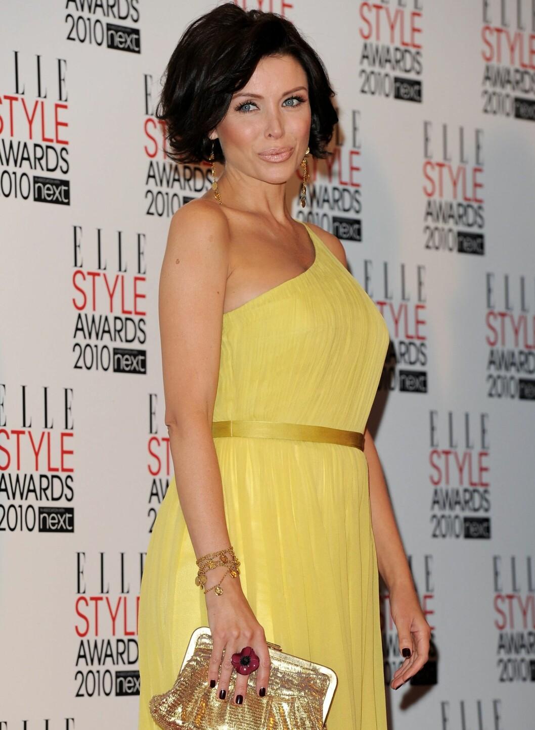 Dannii Minogue i en solgul, asymmetrisk kjole. Til denne kjolen har hun valgt gullfargede detaljer, som veske, armbånd og øredobber.  Foto: All Over Press