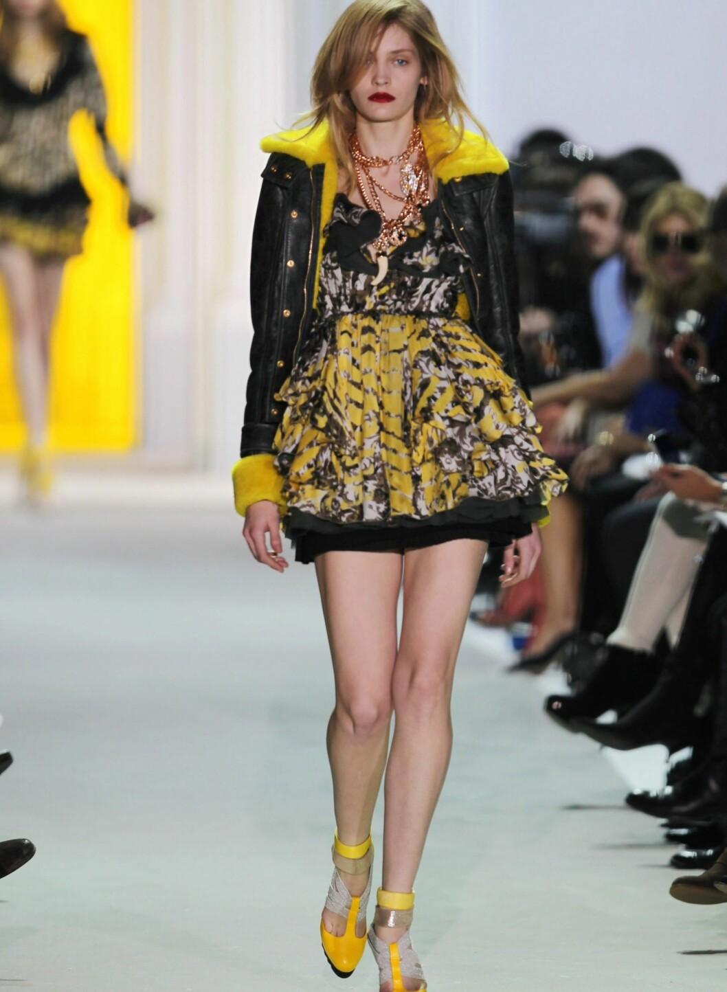 På Just Cavallis show under moteuka i Milano kunne vi se denne looken. Her har modellen fått gule sko, en gulspettet kjole og en jakke med gul pelskant. Det trenger altså ikke være så mye gult før kyllinglooken kommer. Vi kan også notere oss at et småsurt uttrykk ikke er helt kledelig når man har pyntet seg med fargesirkelens gladeste farge.  Foto: All Over Press