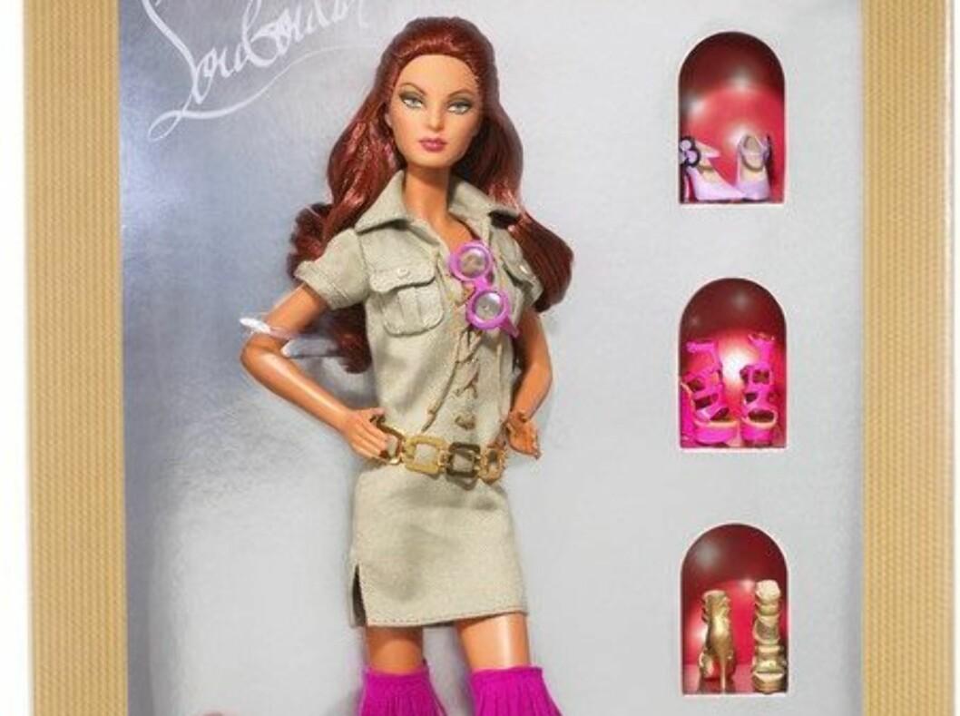 Dette er Loubotin-Barbie. Hun kommer med minikjole, fuksiafargede støvletter, og selvsagt flere sko med den karakteristiske røde sålen. Er hun superkul, eller er det tragisk å bruke penger på noe slikt? Si din mening nederst i artikkelen. (Ca kr 1200, Net-a-porter.com). Foto: Net-a-porter.com