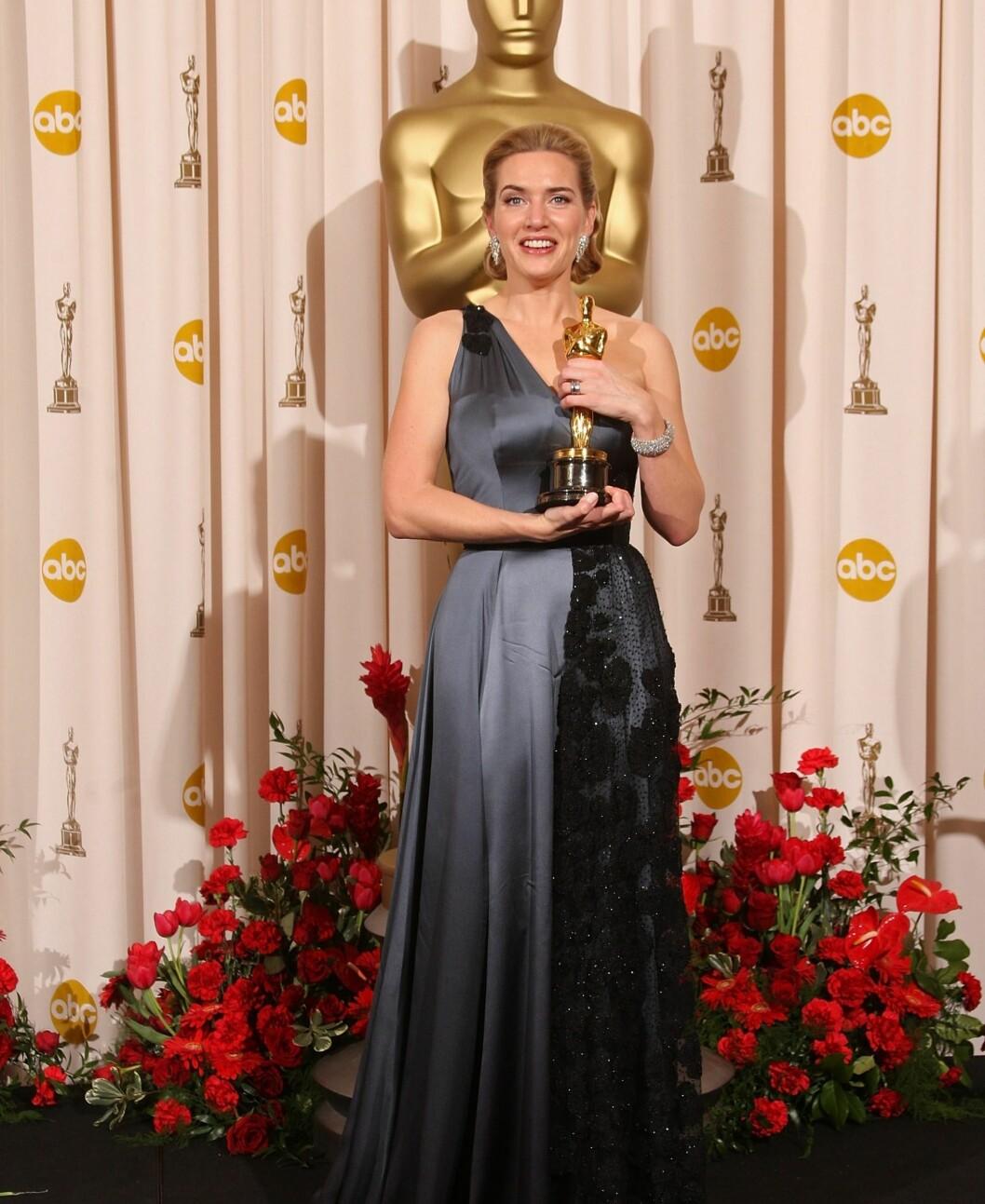 En glad Kate Winslet med Oscar-statuetten sin og en asymmetrisk kjole. Foto: All Over Press