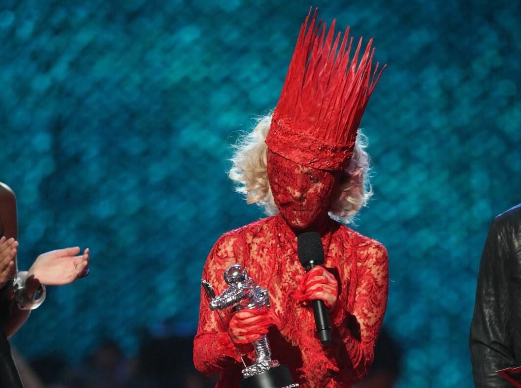 Det er vanskelig å ikke bli lagt merke til i blondedekket ansikt og flammelignende hatt. Foto: All Over Press