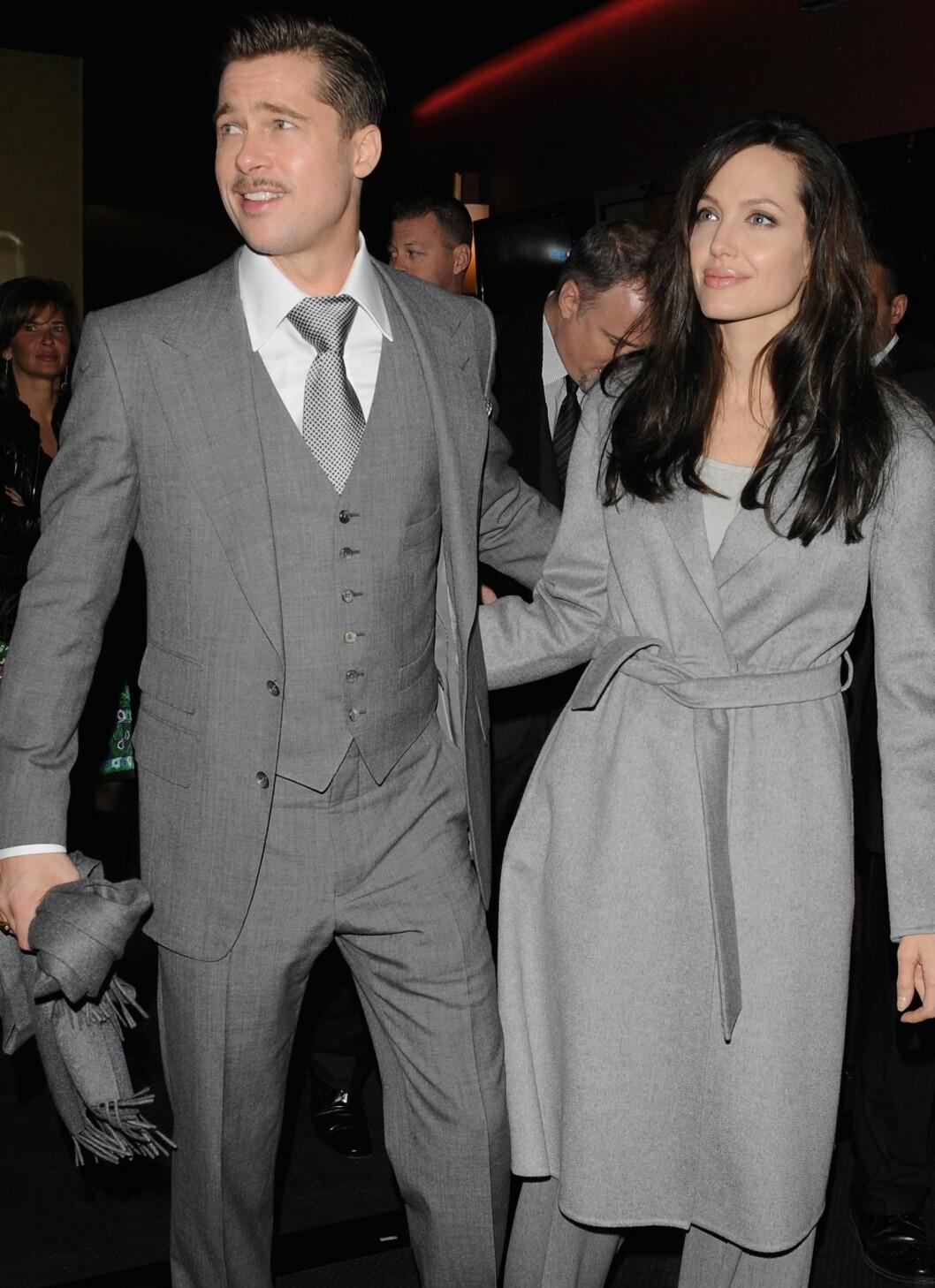 Brad Pitt og Angelina Jolie kjører her begge en grå gentleman-stil. Han i skjorte og dress, hun i dressbukse og trenchcoat.  Foto: All Over Press