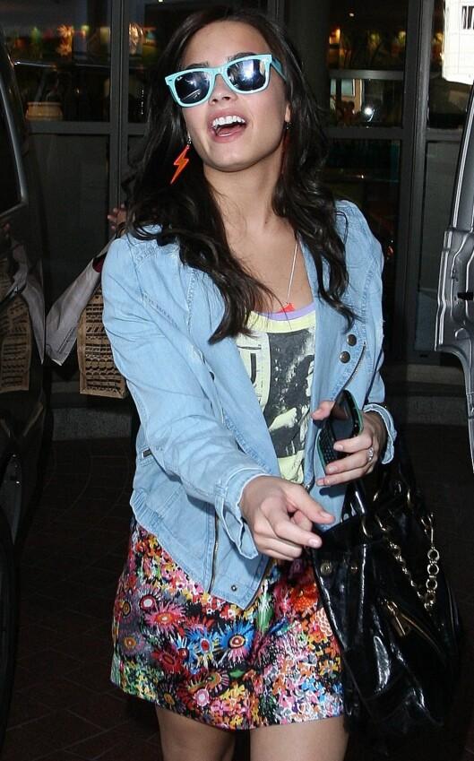 I 80-TALLSSTIL: Skuespiller Demi Lovato i fargerikt silkeskjørt som er pyntet ned med slitt olajakke og rocka t-skjorte. Legg merke til de turkise solbrillene. De er sommerens store slager!  Foto: All Over Press