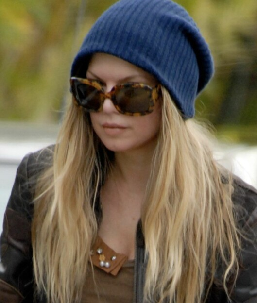 Fergie skjuler nesten hele ansiktet bak solbriller og en stor, blå lue. Foto: All Over Press
