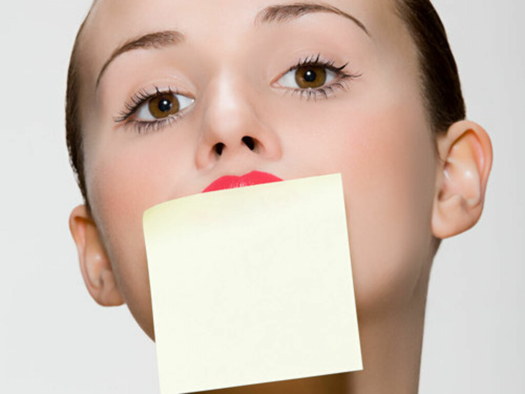 Woman with adhesive note on her mouth Foto: Image Source