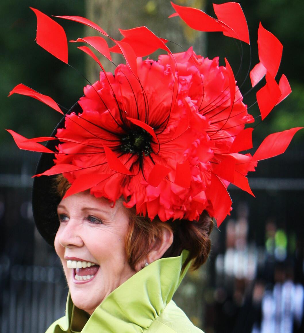 En strålende opplagt Cilla Black, Englands 60-talls popstjerne og tv-kjendis, med en enorm rød blomst snedig dandert på hodet på årets Ascot.  Foto: All Over Press
