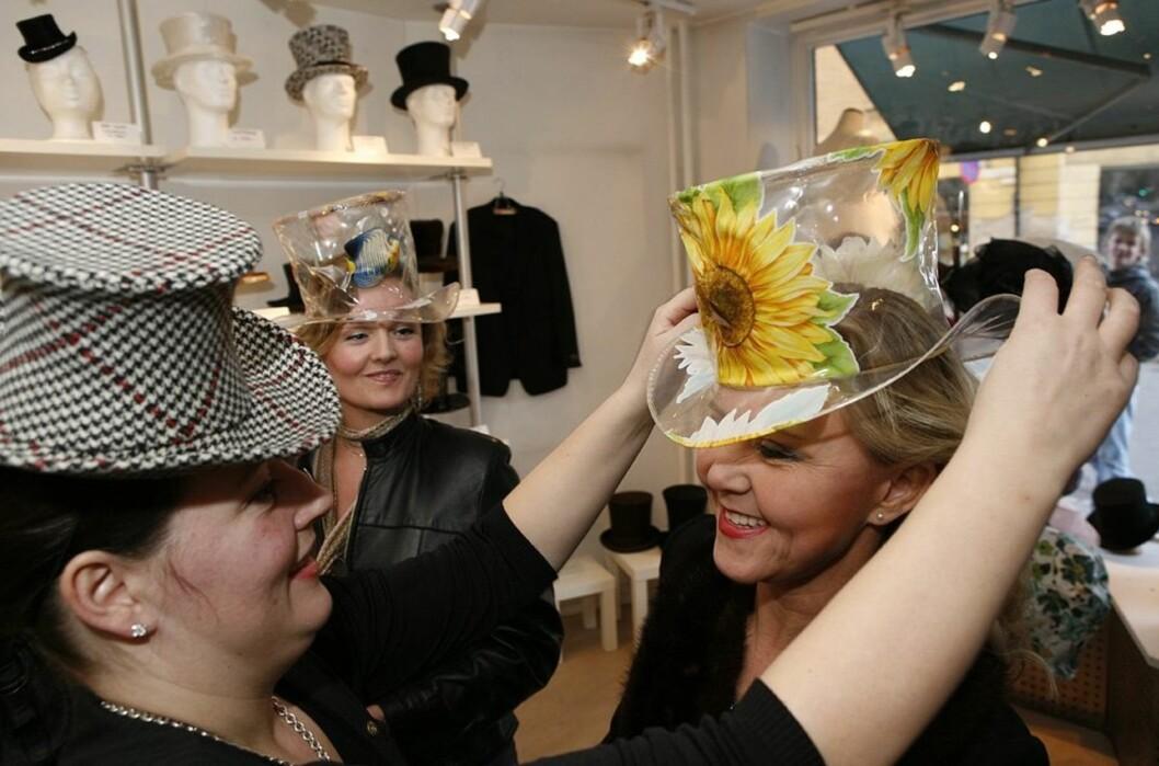 Designerne har laget flosshatter i alle slags materaler, som filt, silke og lakk. Hatter til fest, bryllup og jakt. Men med så mye regn som man har hatt i vinter måtte de kline til med en regnfloss også. Slik ble en plastduk gjort om til flosshatt. Med muntre solsikker på. Her danderer Åse hatten på hodet til Iren Christina.