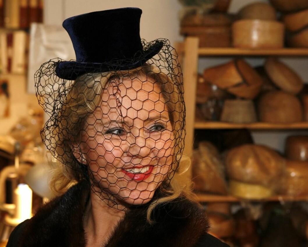 Iren Christina med dyp blå minifloss i fløyel på hodet. Hatten er laget av moderne silkefløyel pyntet med grovmasket slør.