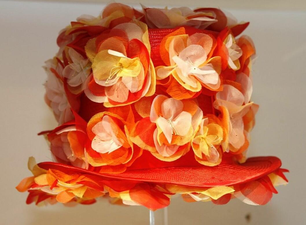 Flosshatt i forkledning lik en blomstereng. Hatten er overstrødd med håndlagede blomster i silkeorganza.