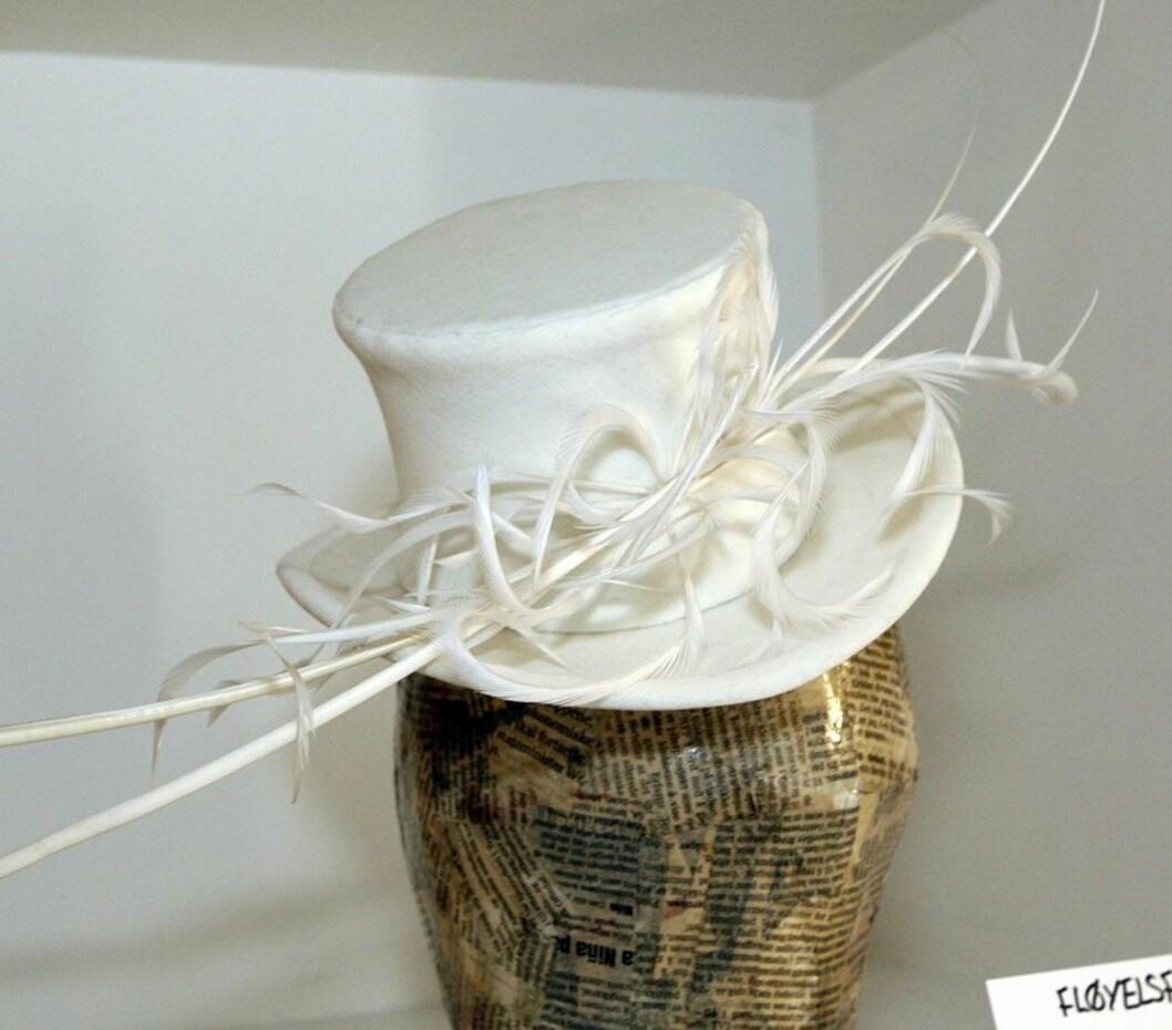 Ingen grunn til at bare brudgommen skal få gå med flosshatt, synes Åse. Hatt laget av hvit fløyel og pyntet til fest med hvite fjær.