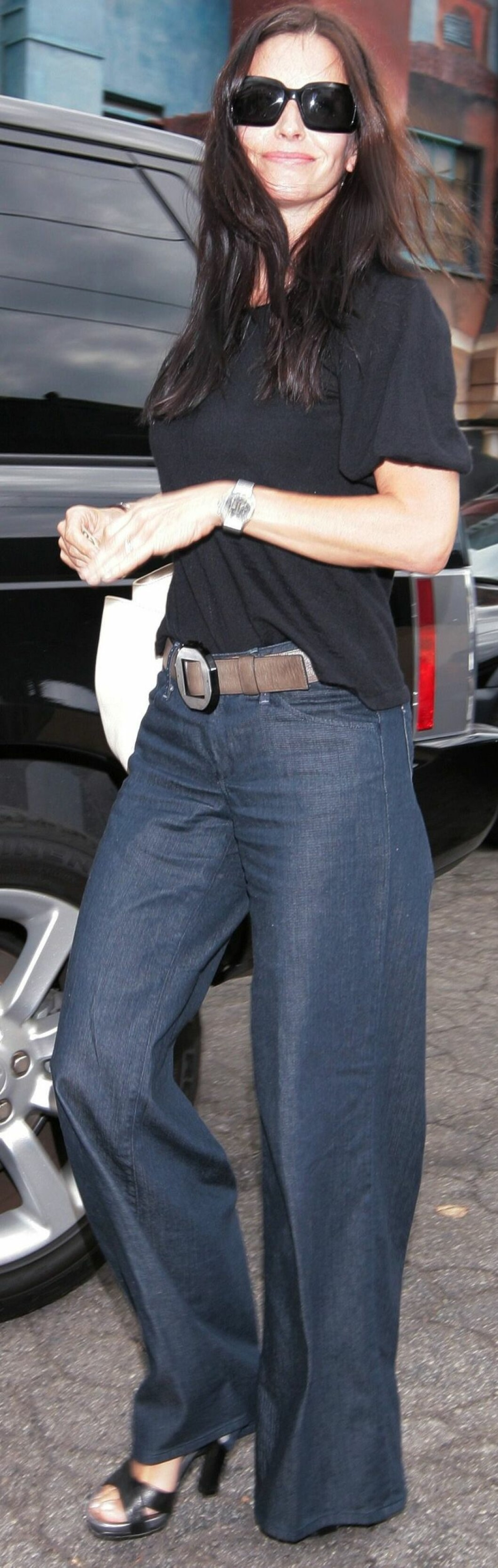 Courtney Cox ser sofistikert ut i sine 70-talls solbriller, midtskill og vide bukser.