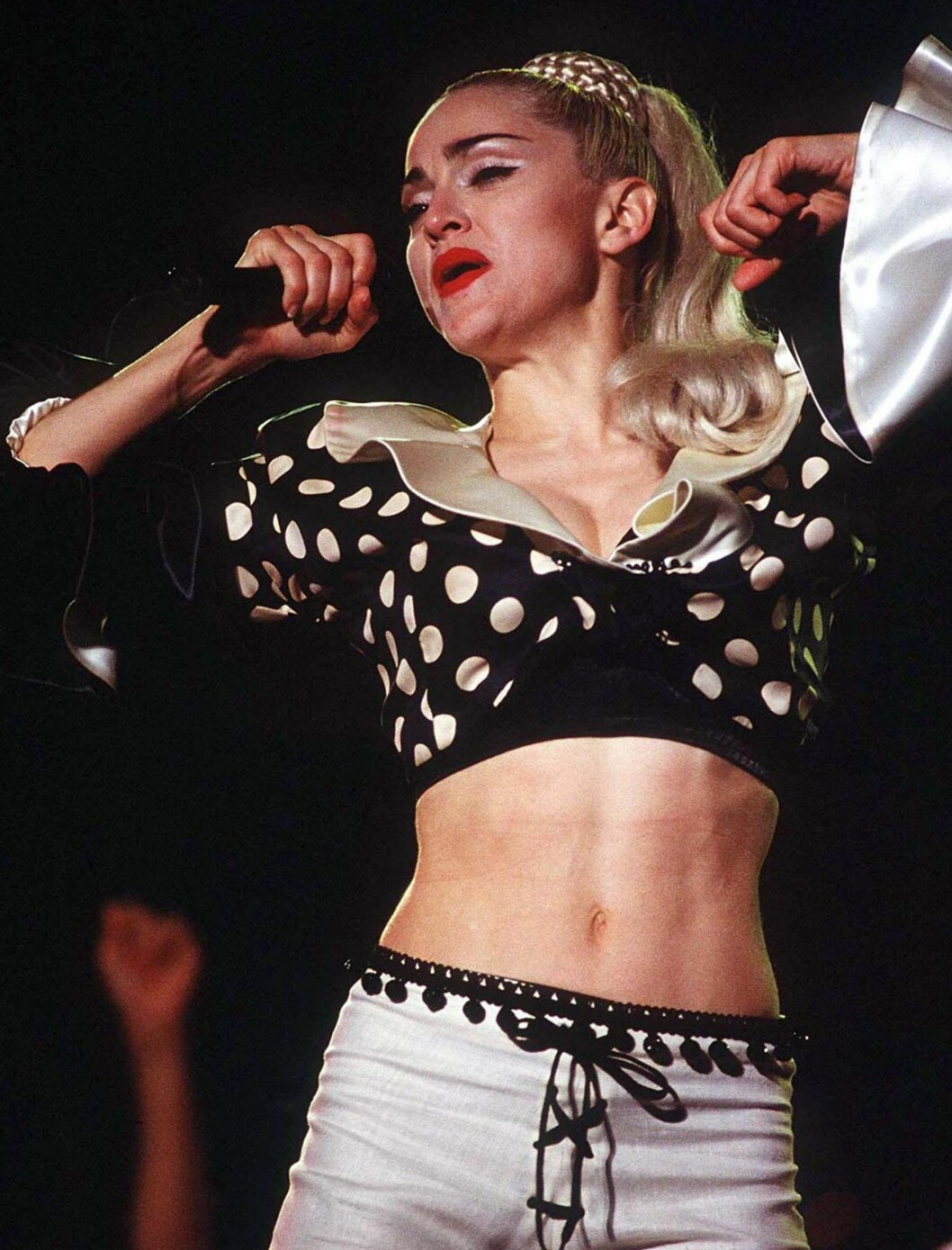 Polkadot-bluse og hvite bukser under «Blond Ambition World Tour».