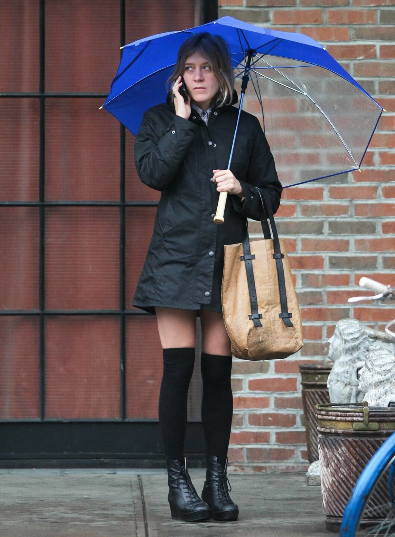 Skuspiller og moteikon Chloe Sevigny ute en regnværsdag i knestrømper, snørestøvletter og frakk. Legg merke til den store paraplyen i trendy kongeblå med transparente partier. Foto: All Over Press