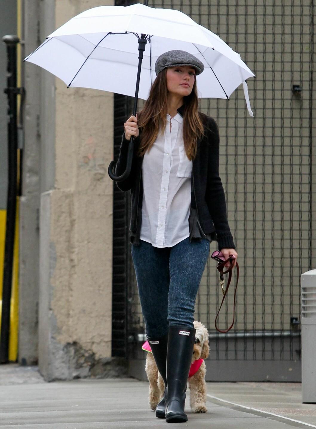 Friday Night Lights-skuespiller Minka Kelly er søt i sixpence, støvler og hvit paraply over hodet. Foto: All Over Press