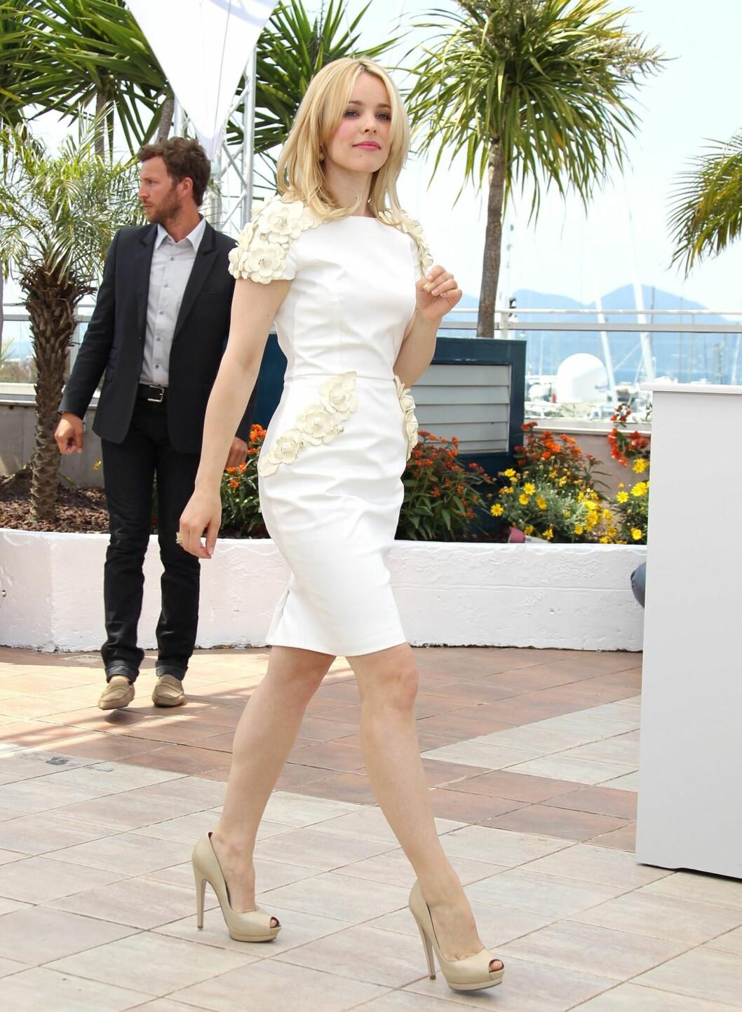 Rachel McAdams strålte også i hvitt under fotoshooten i Cannes. Hennes knelange Maxime Simoens-kjole med blomsterdekorasjoner falt også i smak hos fotografene. De nude peeptoe-skoene forlenger skuespillerens legger.  Foto: All Over Press
