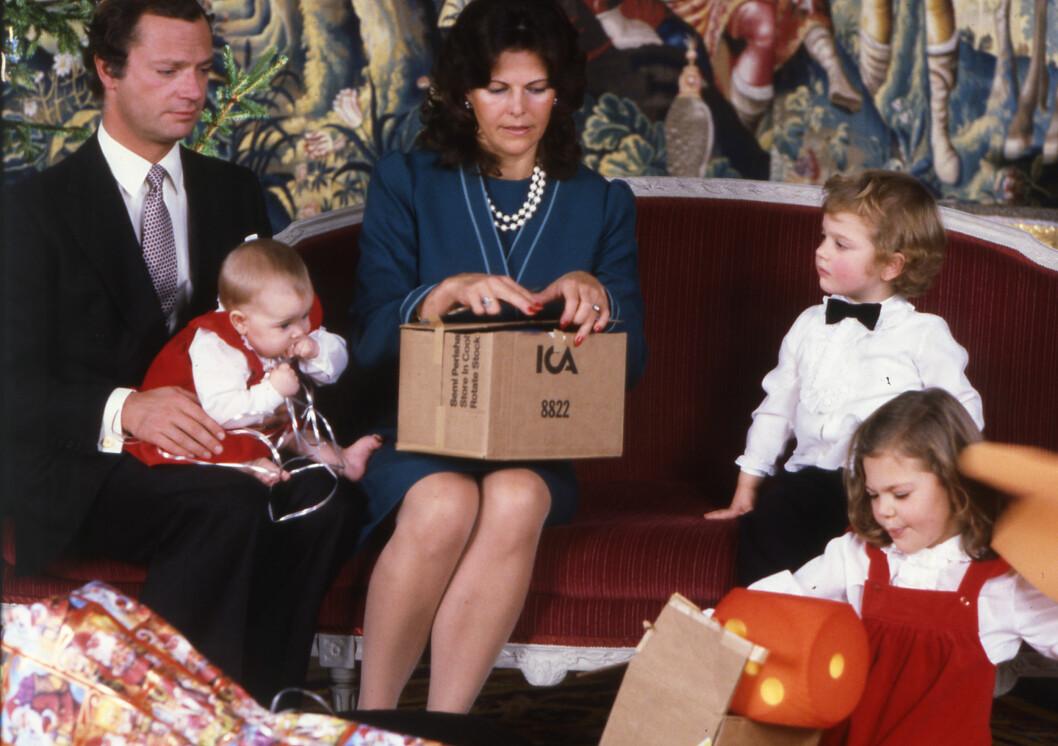 ANNO 1982: Kong Carl Gustaf og dronning Silvia fotografert julen 1982 på slottet i Stockholm. Prinsesse Madeleine på fanget til sin far, mens prins Carl Philip og kronprinsesse Victoria entusiastisk åpnet gaver. Foto: NTB Scanpix