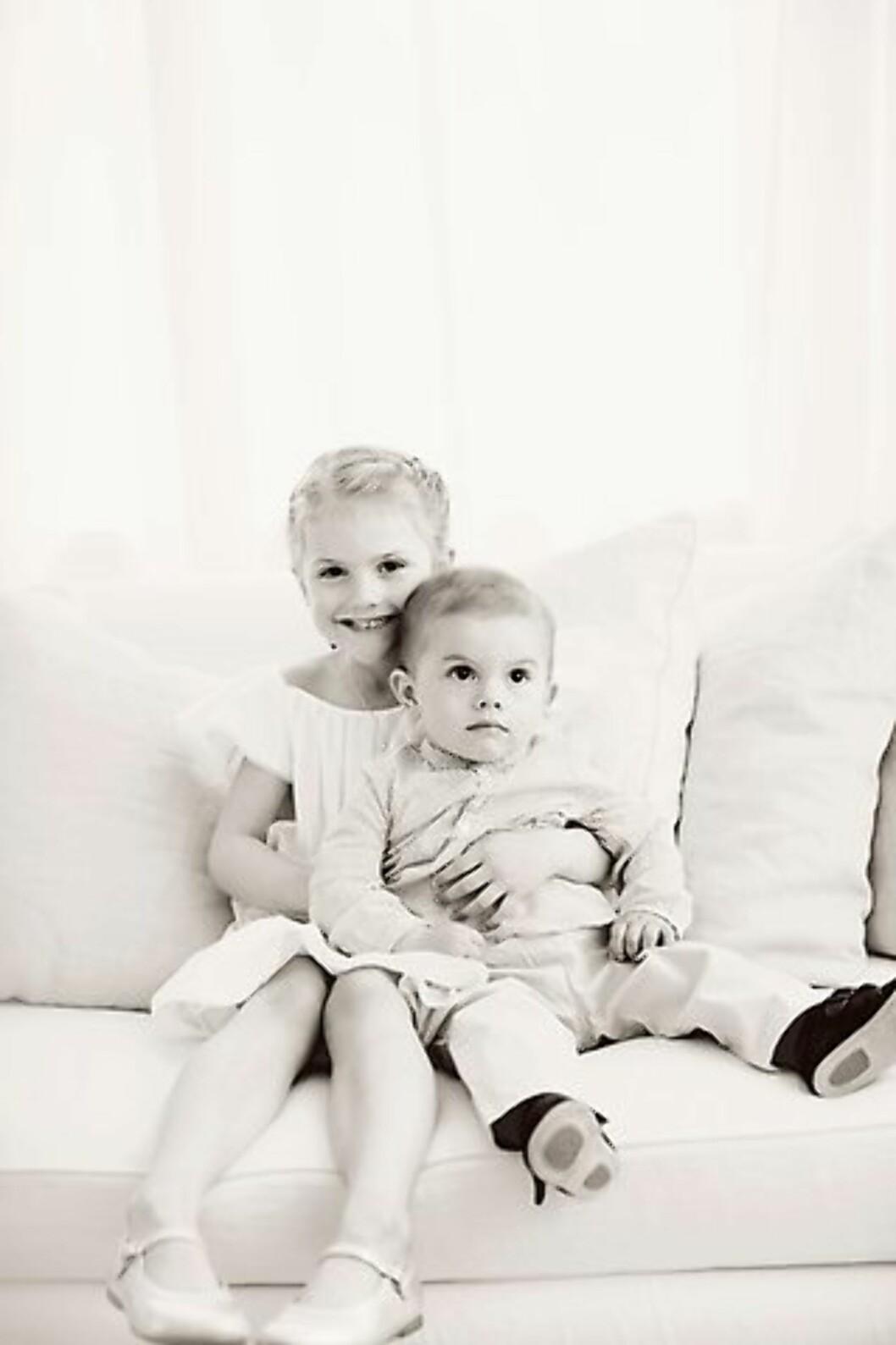 BROR OG SØSTER: Det er fire år som skiller prinsesse Estelle og prins Oscar. Han sitter trygt i sin søsters favn. Foto: Erika Gerdemark / Kungahuset.se
