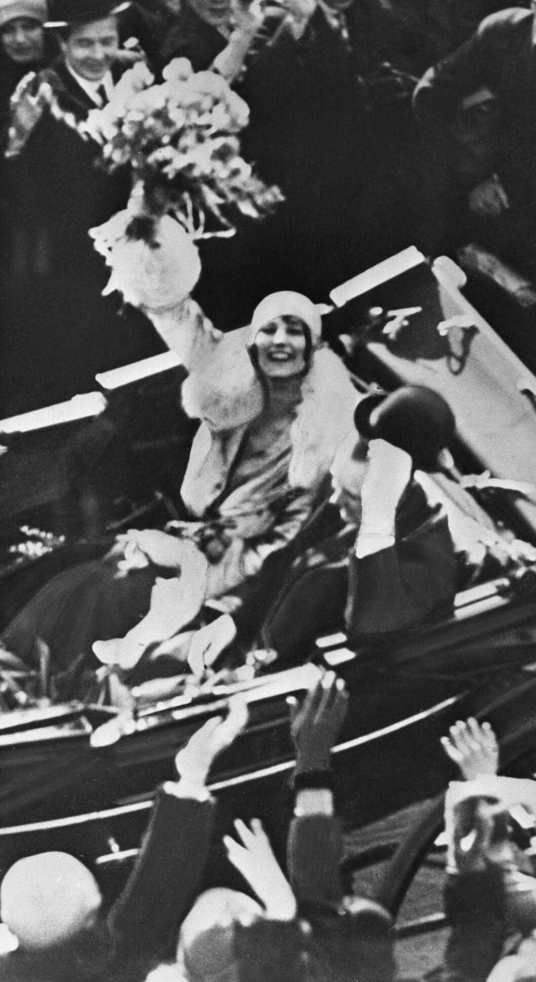 LYKKE: Prinsesse Märtha og kronprins Olav i åpen vogn på rundtur gjennom hovedstaden før sitt bryllup. Her vinker en tydelig lykkelig prinsesse Märtha med blomsterbukett i hånden.  Foto: NTB Scanpix