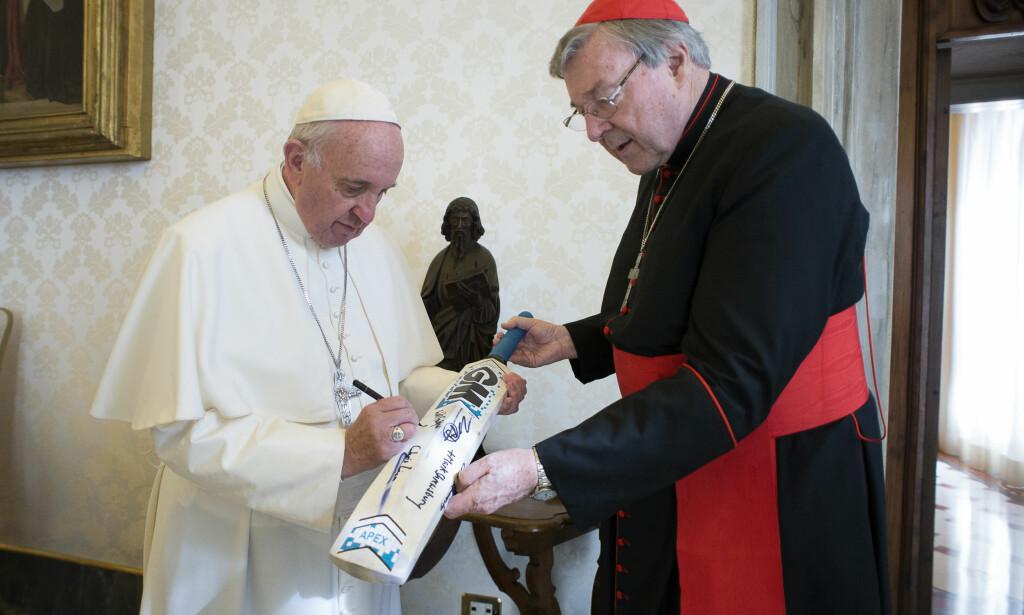 KRISE: I lykkeligere dager, som her i oktober 2015, kunne pave Frans og kardinal George PeIl more seg med ei cricket-kølle. Nå er pavens nære medarbeider sendt hjem til Australia på permisjon for å forsvare seg mot en tiltale for seksuelle overgrep mot mindreårige. Foto: L'Osservatore Romano / AP / NTB Scanpix