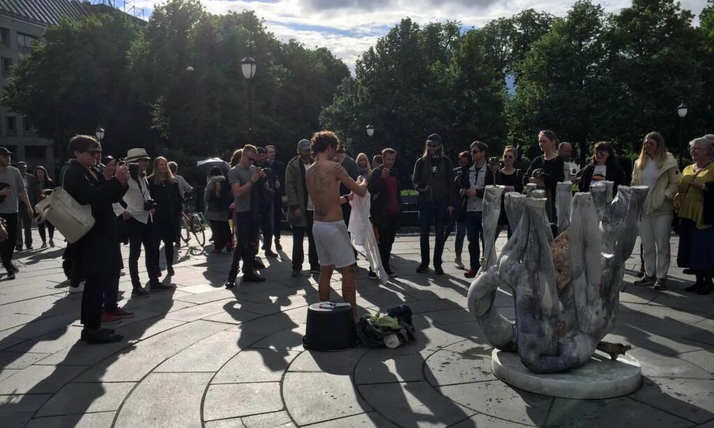 AVDUKING: Lars Brekke avslutter sin performance under åpningen og avdukingen av Sverre Gullesens Galleri Bunt på Eidsvolls Plass. Begge deler er del av årets Norsk skulpturbiennale, som ellers er å se på Vigeland-museet. FOTO: Arve Rød