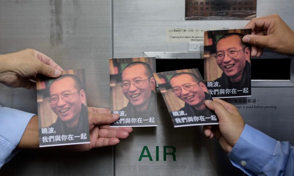DEMONSTRASJONER: Demonstranter forbereder seg på å sende postkort til den dødssyke Nobelpris-vinneren Liu Xiaobo (avbildet på kortene), som nå er sluppet ut av fengselet for å få behandling på et sykehus i Shenyang. Foto: ANTHONY WALLACE / AFP / NTB Scanpix