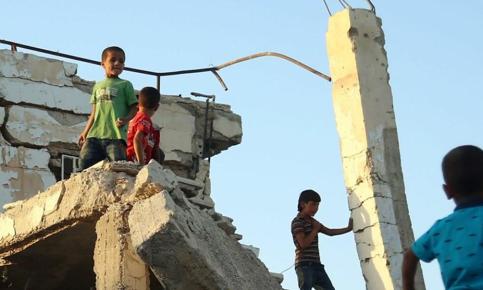 TØFT LIV: Syriske barn, som flyktet fra hjemmene sine i al-Marj-byen i Ghouta, leker i ruinene av en bydel i al-Nashabiyah i Øst-Ghouta. Øst-Ghouta ligger like utenfor hovedstaden Damaskus, og kontrolleres av opprørere som kjemper mot Bashar al-Assad og hans regime. Det får de drøye 400 000 innbyggerne i Øst-Ghouta merke på kroppen: Byen beleires av Assads regjeringsstyrker og deres allierte, og knapt noe mat og medisinsk hjelp kommer inn hit. Foto: Amer Almohibany / AFP / NTB Scanpix