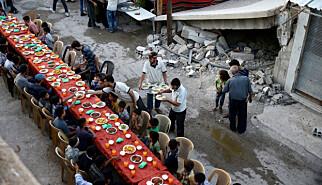 RAMADAN-FEST: Under ramadan fikk de rundt 400 000 innbyggerne i Øst-Ghouta gratis måltid, som ble feiret på langbord i en av de mange ruingatene i byen. Foto: Bassam Khabieh / Reuters / NTB Scanpix