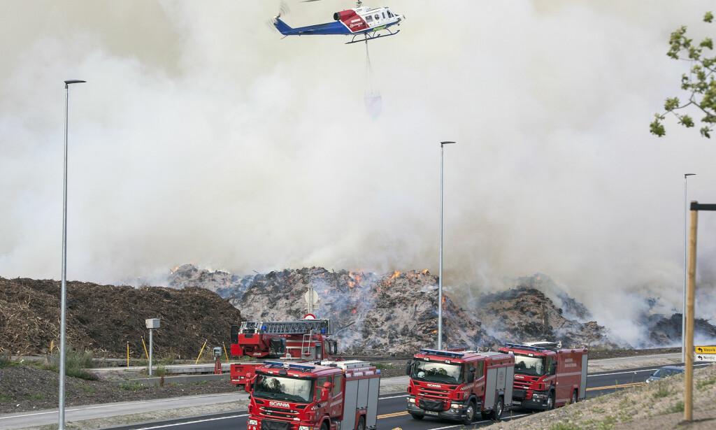 BARKEBRANN: Brannvesenet setter inn helikopter i slokkingen av en omfattende ulmebrann i et barkanlegg på Sky i Larvik lørdag. Sterk røykutvikling truer både naboer og trafikk. Foto: Peder Torp Mathisen / NTB scanpix
