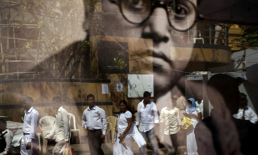 HEDRES: Indere går forbi bildet av avdøde Bhimrao Ambedkar, som var et medlem av en av de mange lavkastene i India. Ambedkar er sett på som en av Indias mest prominente frihetskjemperne. Han var også sjefsarkitekten til den indiske grunnloven, som forbød kaste-diskriminering. Foto: Rajanish Kakade / Ap / Scanpix
