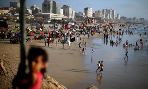 SOMMERIDYLL. ELLER? Palestinere i Gaza på stranda på en av de alltid varme sommerdagene denne måneden. I motsetning til i Norge, er du garantert minimum 30 grader daglig, som oftest nærmere 40. Når elektrisiteten er fraværende - og drikkevannet likeså - føles livet til de rundt to millioner innesperrede menneskene forferdelig. Foto: Mohammed Salem / Reuters / Scanpix
