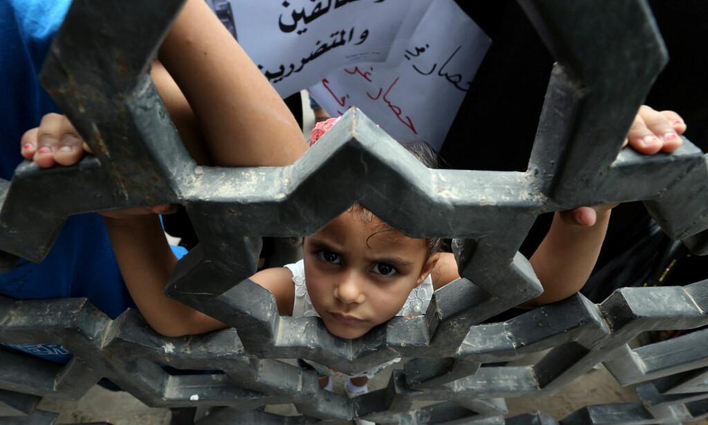 SPERRET INNE: En palestinsk jente ser ut gjennom Rafah-porten, som er grensa mellom Gaza og Egypt. Siden 2015 har denne grensa vært så godt som hermetisk stengt, som gjør at palestinerne i Gaza er sperret inne på det som er et av verdens tettest befolkede områder. Foto: Ibraheem Abu Mustafa / Reuters / Scanpix