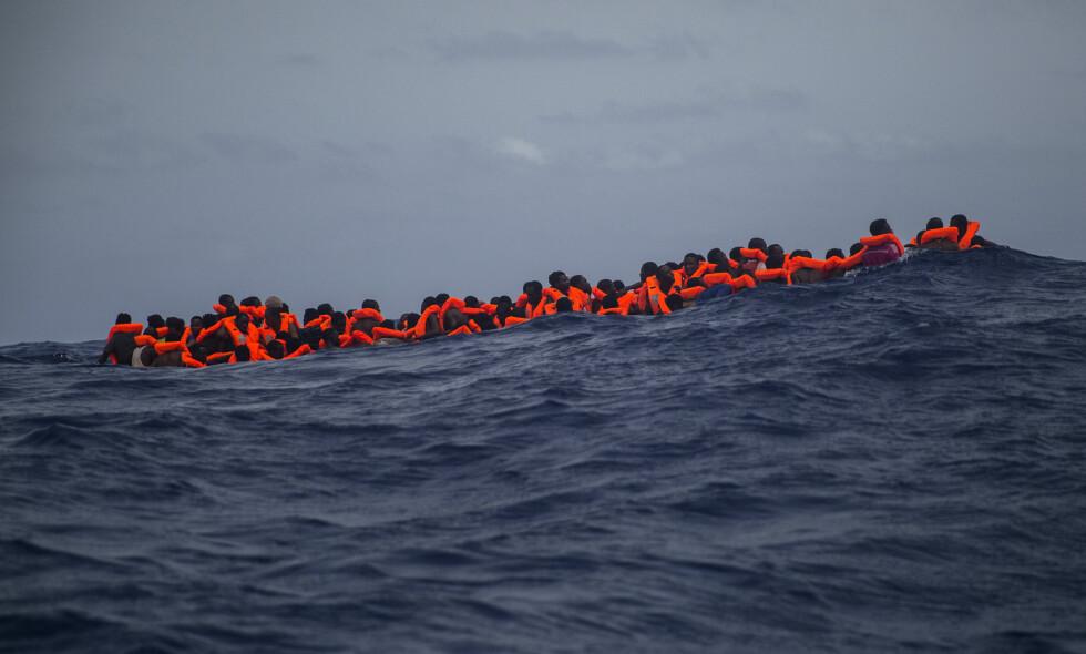 RISIKERER LIVET I MIDDELHAVET: Her venter flyktninger i Middelhavet nord for Libya på å bli reddet av hjelpearbeidere fra den spanske NGOen Proactiva Open Arms tidligere i sommer. Foto: Santi Palacios / AP Photo / NTB scanpix
