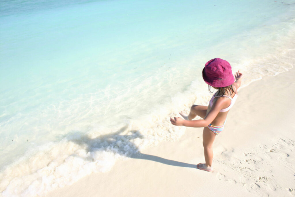 child playing  at the beach  in the maldives