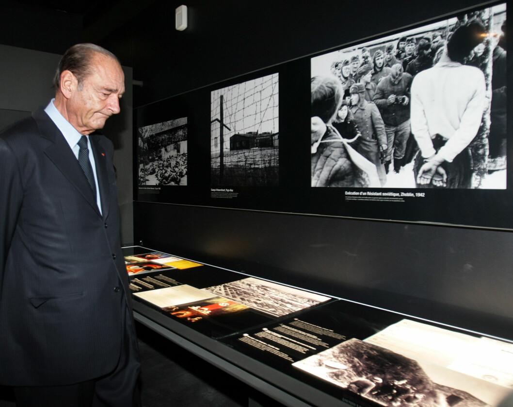 HEDRET MINNENE: Den daværende franske presidenten, Jacques Chirac, var i november 2005 på besøk i Natzweiler og tok seg tid til å se på  dokumenter og bilder fra den eneste tyske Nazi-leiren på fransk jord. Her satt 504 nordmenn i perioden 1941 til 1944. Foto: NTB Scanpix