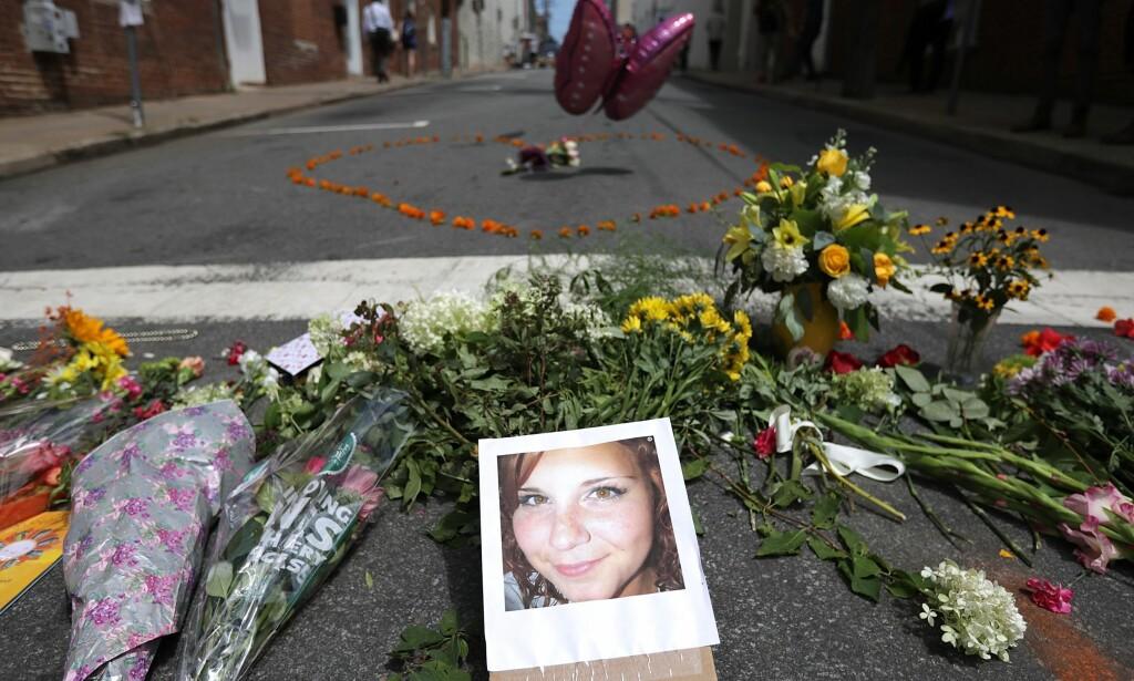 SØRGER: Folk har lagt blomster og bilde av 32 år gamle Heather Heyer, som ble drept da en såkalt hvit nasjonalist kjørte inn i en gruppe mennesker som demonstrerte mot nynazistene og de hvite nasjonalistene, som holdt en demonstrasjon. Foto: Chip Somodevilla / Getty / Afp / Scanpix