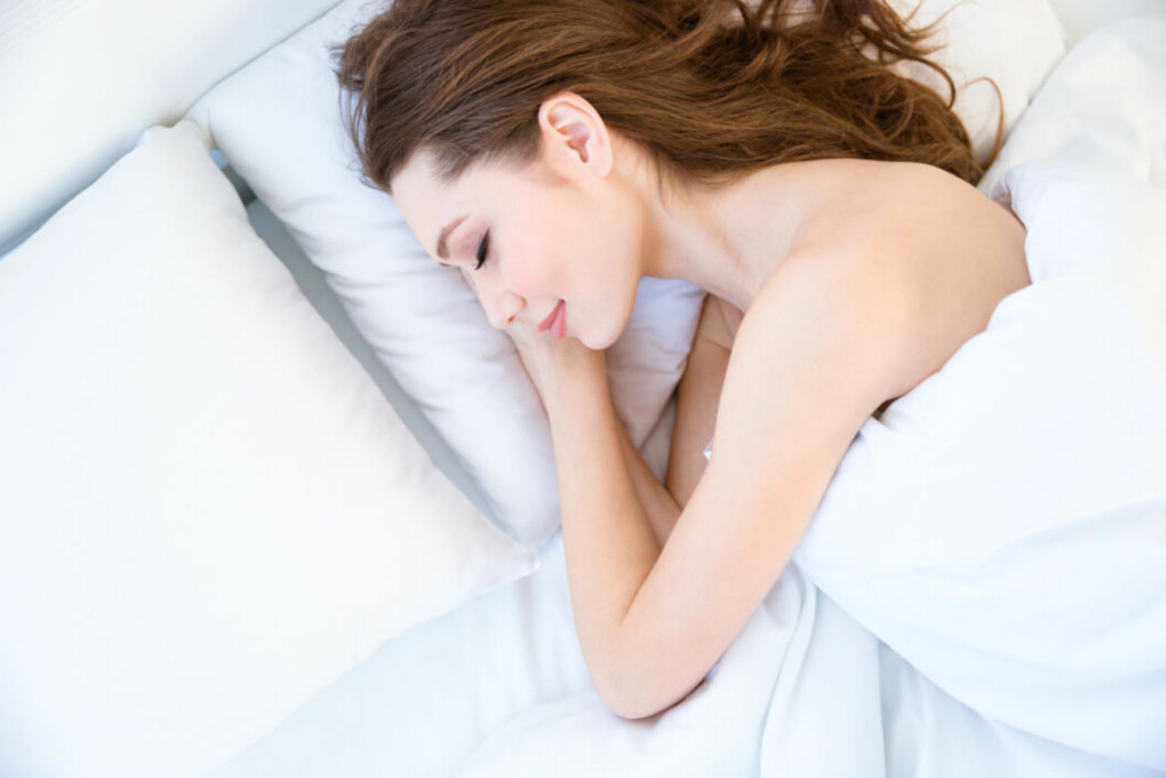 Top view of tired beautiful young woman with long hair sleeping on bed in bedroom