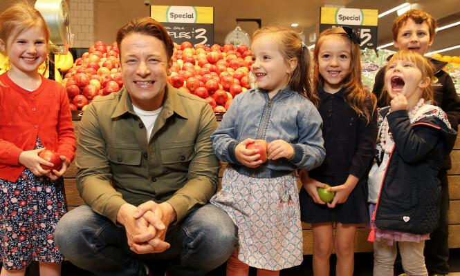 BARNAS AMBASSADØR: Jamie Oliver har markert seg som forkjemper for bedre mat til barn, ikke minst i skolen. Han reiser verden rundt og bruker sin innføytelse. Her omgitt av barn og sunn mat på åpningen av en Woolworth -butikk i Australia. Foto: SHUTTERSTOCK