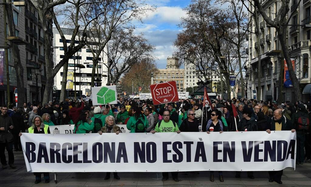 OPPRØR: I Spania snakkes det om «turismofobi» blant de fastboende. Demonstranter i hovedgata Las Ramblas bærer et banner der det står: «Barcelona er ikke til salgs». De fastboende er i opprør mot alle feriegjestene som ødelegger byen deres og krever enda flere tiltak fra byens myndigheter. Foto: AFP / NTB Scanpix / LLUIS GENE