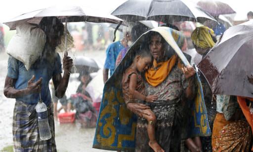 PÅ VEI I TRYGGHET: Rohingya-flyktninger forsøker å unnslippe regnet med paraplyer og tepper, mens de håpefullt venter på å komme seg inn i nabolandet Bangladesh. Foto: Mohammed Ponir Hossain / Reuters / Scanpix