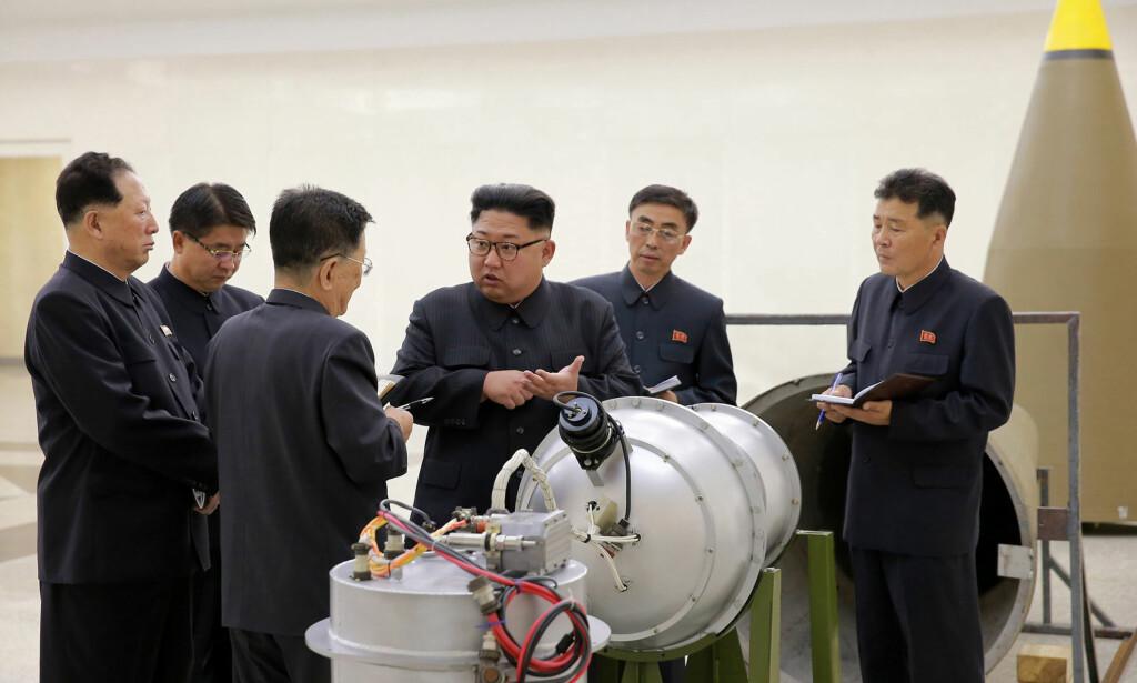 BOMBE: Nordkoreanske myndigheter publiserte søndag dette bildet som angivelig viser landets leder Kim Jong-un idet han inspiserer en hydrogenbombe som blir lastet inn i en rakett. Foto: AP / NTB scanpix