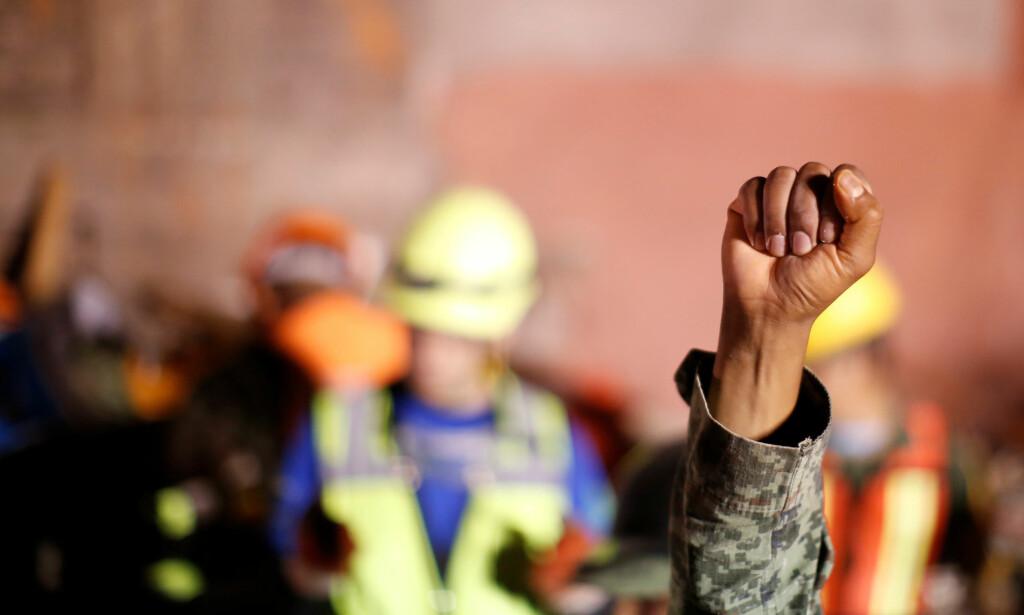 LYTTER: Med jevne mellomrom ble knyttnevene til redningsarbeidere løftet i været, som et tegn til alle om at de måtte være stille. De skulle lytte etter tegn til liv. Nå skjer dette stadig sjeldnere. Foto: Carlos Jasso / Reuters / NTB Scanpix