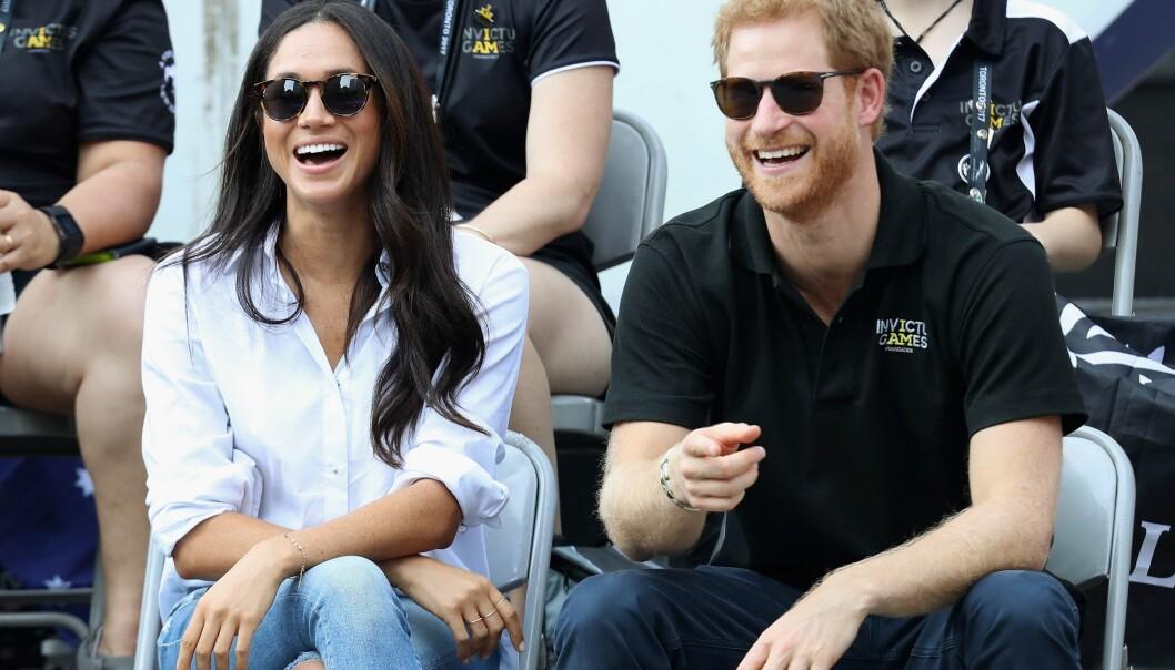 GOD STEMNING: Latteren satt løst mellom prins Harry og kjæresten Meghan Markle under tennis-eventet. FOTO: NTB Scanpix