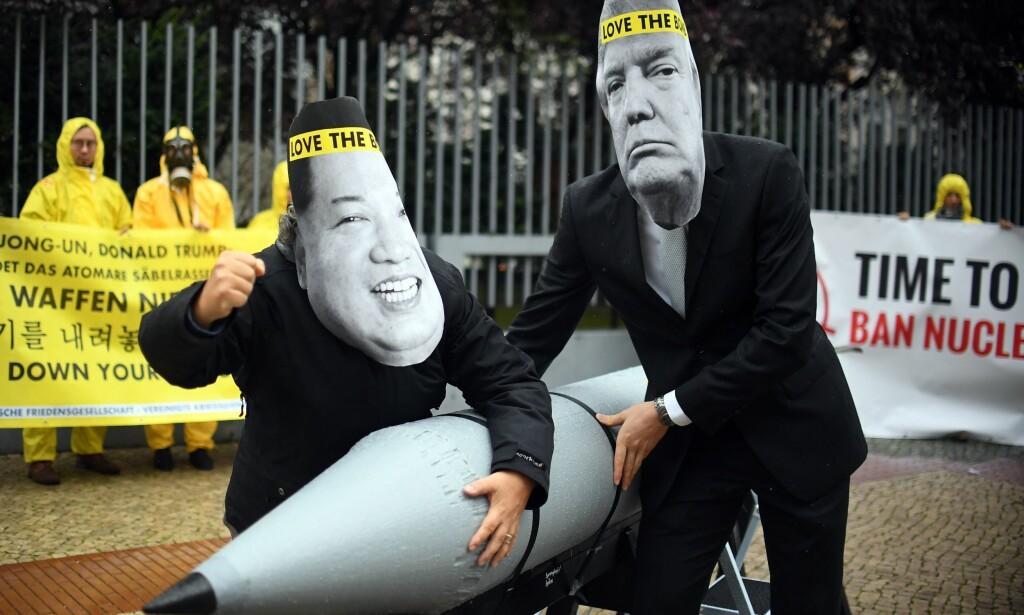 VÅPENRASLERE: Medlemmer av ICAN demonstrerer mot atomvåpen utenfor USAs ambassade i Berlin i september i år med masker av USAs president, Donald Trump, og Nord-Koreas leder, Kim Jong-un. Foto: AFP / NTB Scanpix / dpa / Britta Pedersen