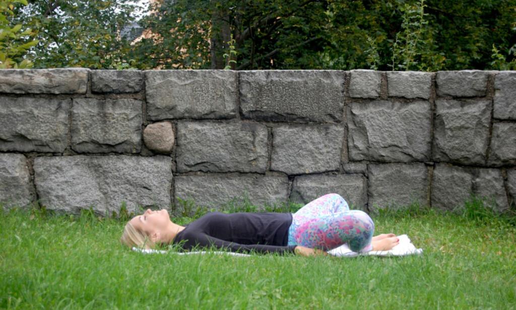HVILENDE BUDDHA: Avslutt med å legge deg ned på ryggen og slappe av. Legg armene nedover langs siden, og trekk bena dine ut mot siden slik at fotsålene hviler mot hverandre. FOTO: Johanna Bengtsson
